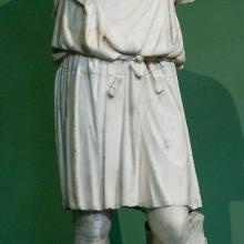 Exomis, Kopie einer Statue aus dem 4. Jhd. Quelle: https://upload.wikimedia.org/wikipedia/commons/f/f0/Young_man_exomis_Musei_Capitolini_MC892.jpg